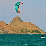 Kite surfer sailing by offshore island