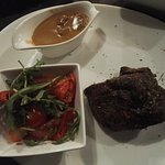Steak with mushrooms sauce and salad of Belgian tomatoes.