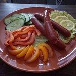 Охотничьи колбаски, подаются с гарниром из свежих овощей.