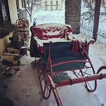 Snow covered sleigh on the front porch