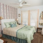 Azalea Suite with Queen bed, sitting area with day bed, mini fridge, flat screen TV.
