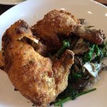 Fried chicken, normally served with mashed potatoes, served atop sautéed greens and rice.