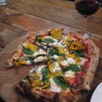 A vegetarian pizza with a glass of Shiraz at Forge Pizzeria