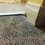 Metal strip at edge of carpet popping up at the corner
