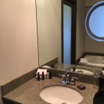 Jetted tub seen in mirror, sliding door for toilet/shower area.