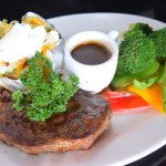 New Zealand Prime Angus Steak, baked potato, grilled vegetables, and gravy.