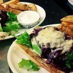 Steak baguette served on a bed of lettuce, topped with red onion jam & cheese