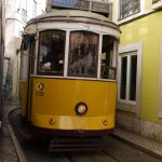 Tram squeezing through the narrow roads of old Lisbon