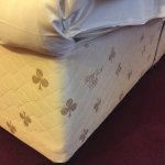 A partially made bed, in a room very much in need of a refurb.