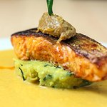 Scottish salmon resting on chickpea gateau, madras fish curry sauce