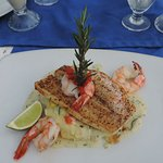 Grilled red snapper with shrimp, on a bed of mashed potatoes and vegetables.