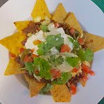 Big bowl of crisp nachos smothered in guacamole,sour cream,Mexican salsa, jalapeños & melted che