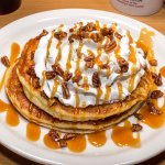 """Heavenly Hot Cakes"" topped with caramel, pecans and whipped cream"