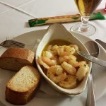 A partly consumed dish of Shelled King Prawns in a suace made with Butter Galic and pepperoncino