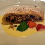 Dessert of home-made aple strudel with almonds and vanilla sauce