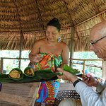 Bill tasting freshly fried plantains and tilapia at Embera Quera villageSandy holding a baby mon