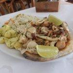 Robalo assado com acompanhamento de frutos do mar, arros e batata assada