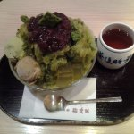 Matcha shaved ice topped with sweet red bean, accompanied with a hot tea