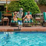 Child jumping into the pool with his parents in the background.