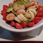 Ensalada de camarones tibios sobre tomate, palmitos, palta y base de verdes