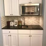 1009kitchen area with 2 flat top burners, microwave, coffee pot, and full size fridge to left of