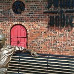 Statue of Truitt Cathy, founder of Chick-Fil-A, with original Dwarf Door behind him