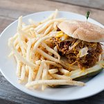 Cowboy pulled pork sandwich with seasoned fries.