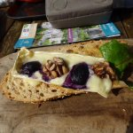 An open brie baguette with 2 half grapes, 2 walnut pieces and a rocket leaf. £4.50