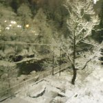 view from hotel room balcony during snowfall at night