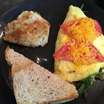 Veggie omelet served with a potato pancake and whole wheat toast.