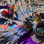 Many head dresses sitting on the ground while their wearers take a break from the festivities.