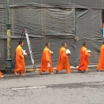 Saffron-robed monks walking to Kim Yong Market