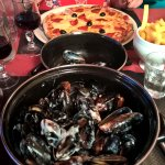 a steaming pot of delicious mussels, wife's pizza in the background
