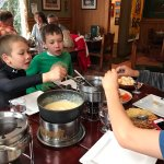 Kids dipping in cheese and beef fondue.