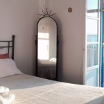 Superior double bed bedroom;with balcony viewing the sea, the sunset setting behind Antiparos..