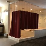 weird, bi-level shower curtain around a huge shower/jacuzzi area