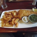 Tasty fish, chips, mushy peas and tartare sauce.