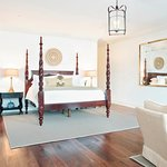 A four-poster bed and hardwood floors in the Charleston City Market Suite