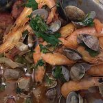Fresh prawns, clams, pork, churiso, coriander, green pepper, tomato, onion, and olive oil.