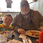 Grandpa has a taco omelet while grandson eats toast, bacon, and sausage