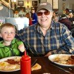 Grandma and grandson enjoy their eggs, toast, and bacon