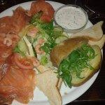 Un plat composé de saumon, de pomme de terre au four, d'une crème à la ciboulette et d'une salad