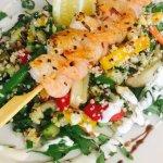 Quinoa-Bulgur-Salat mit Frühlungszwiebeln, Rucola und gebratenem Garnelenspieß.