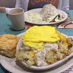 Sausage gray and biscuit in back, front is a biscuit covered with home fries, sausage gravy and