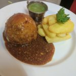 Home made Meat and potato suet pudding hand-cut chips mushy peas and gravy