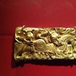 Gold belt buckle with engraving of dragon and bear eating a horse