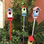 Little bird houses decorating a dining area on the garden ground.
