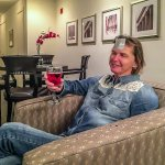 relaxing with a glass of wine and wearing an AKA White House sticker in the living area