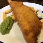 Battered fish chips and mushy peas with ta-tar sauce , relish