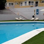 Aspecto piscina con hierba artificial, sombrillas y hamacas